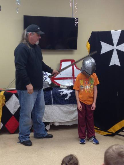 I'd like to say he was being knighted, but this gentleman was trying to prove a point of how armor protects your head!